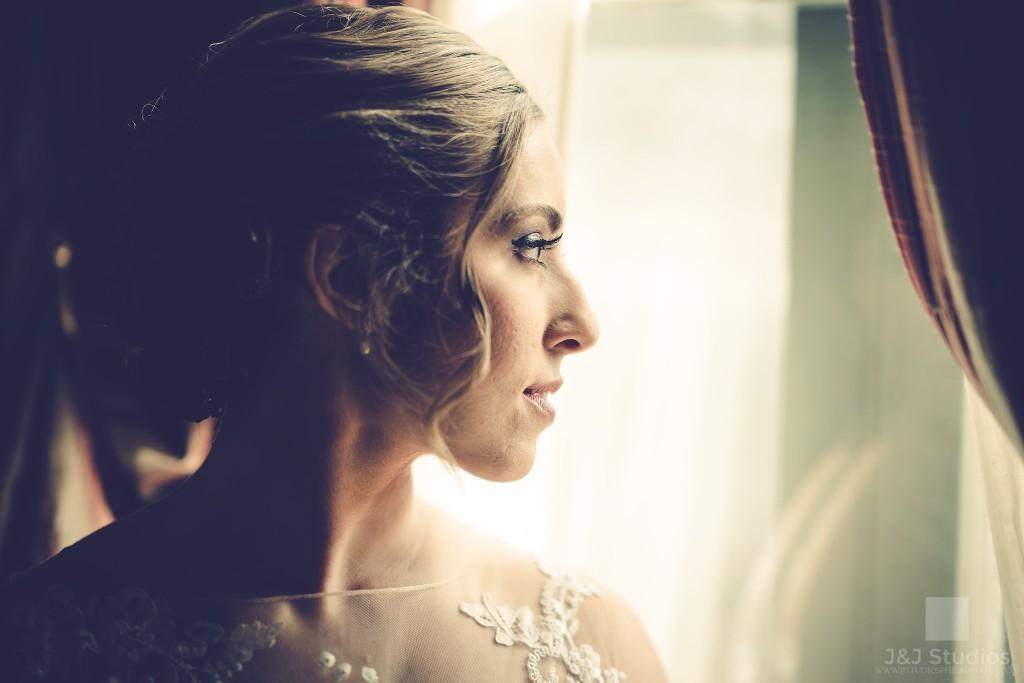 bride looking out window, J&J Studios
